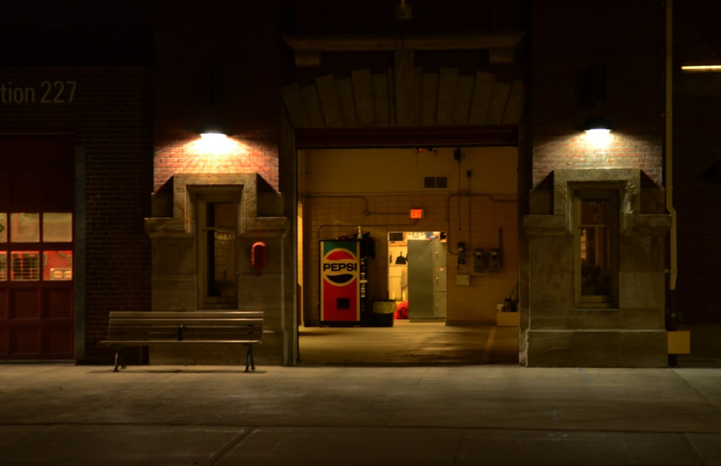night, exterior of firehall 227, open door showing interior and pepsi vending machine, bench on sidewalk,