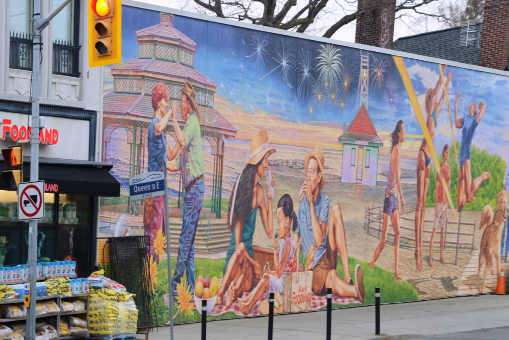 mural on Queen Street East, side of Foodland grocery store, scenes from the beach - a couple dancing by an outdoor pavillion, an Asian family having a picnic in the park, young adults playing beach volleyball, Leuty lighthouse, fireworks in the distance, by John Kuna and Mural Routes