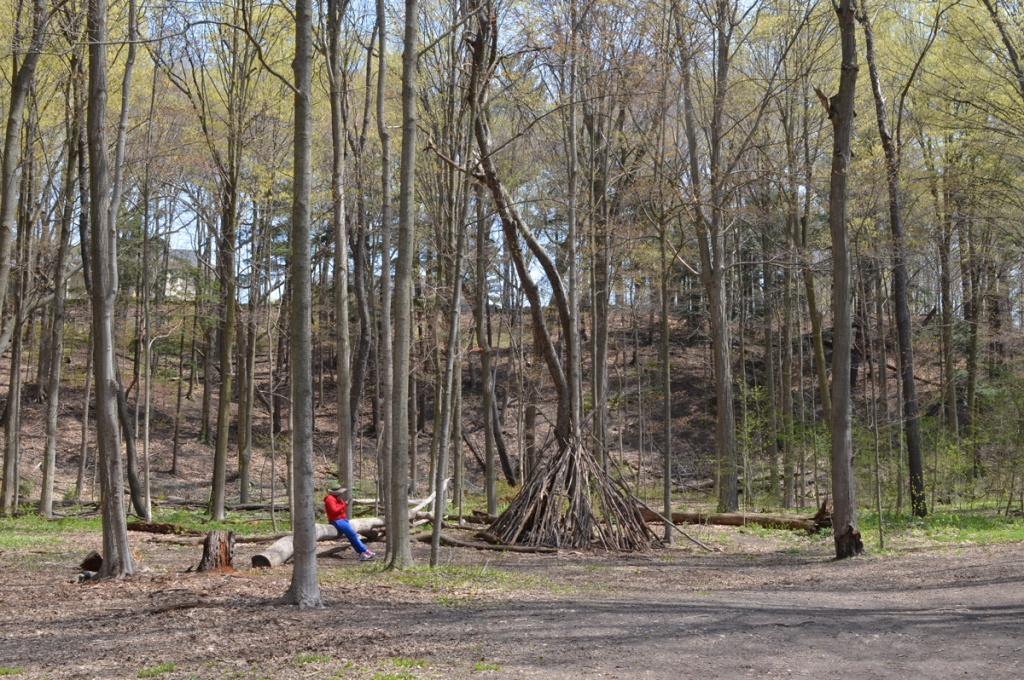 A person in a red jacket sits on a fallen log in a forest beside a teepee shape structure made from tree branches, leaves are just beginning to open, late April