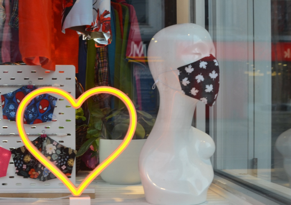 store window with a yellow LED light heart, a white head and shoulders mannequin with closed eyes and wearing a black covid mask with white maple leafs on it.