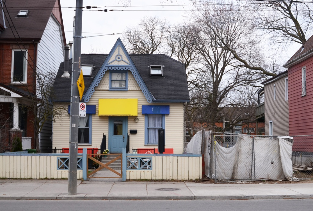 small white house with blue trim and a yellow awning over the front door, white fence around the front yard, empty lot beside it with white tarp covering chainlink fence around the yard