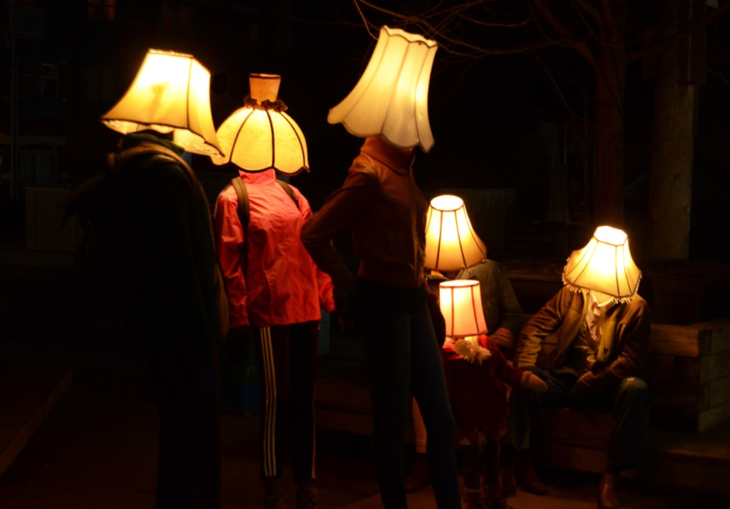 Luminosity art installation of mannequins with lampshades for heads.  night time, so dark outside, lights turned on inside shades