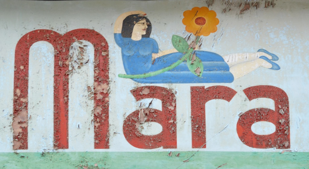old sign above a store doorway, the word Mara with a woman in a blue dress lying across the last 3 letters, holding a big orange and red flower