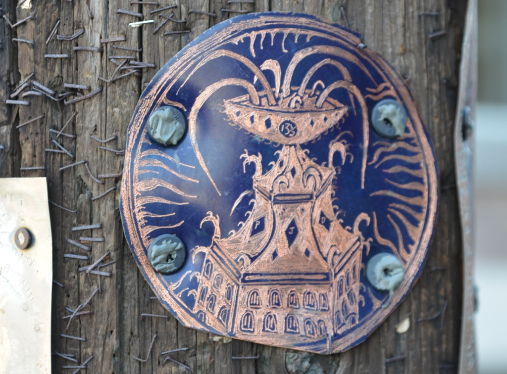 round metal engraving on a small circle, screwed to a wood utility pole.  Design is like a fountain on the top of a building 13 1/2