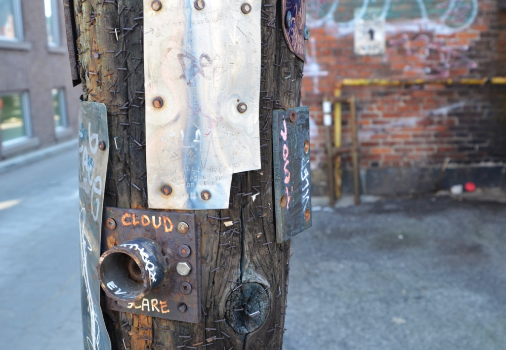 some metal pieces that are graffiti on a pole