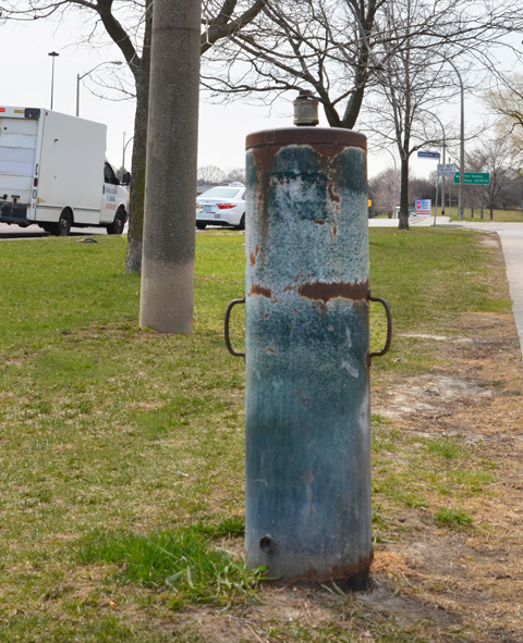 Small cylindrical metal object standing upright on the grass beside a sidewalk, rusty and old