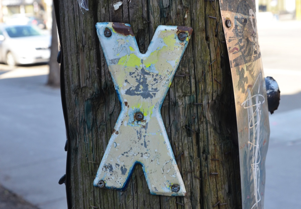 metal in the shape of an X screwed onto a wood utility pole