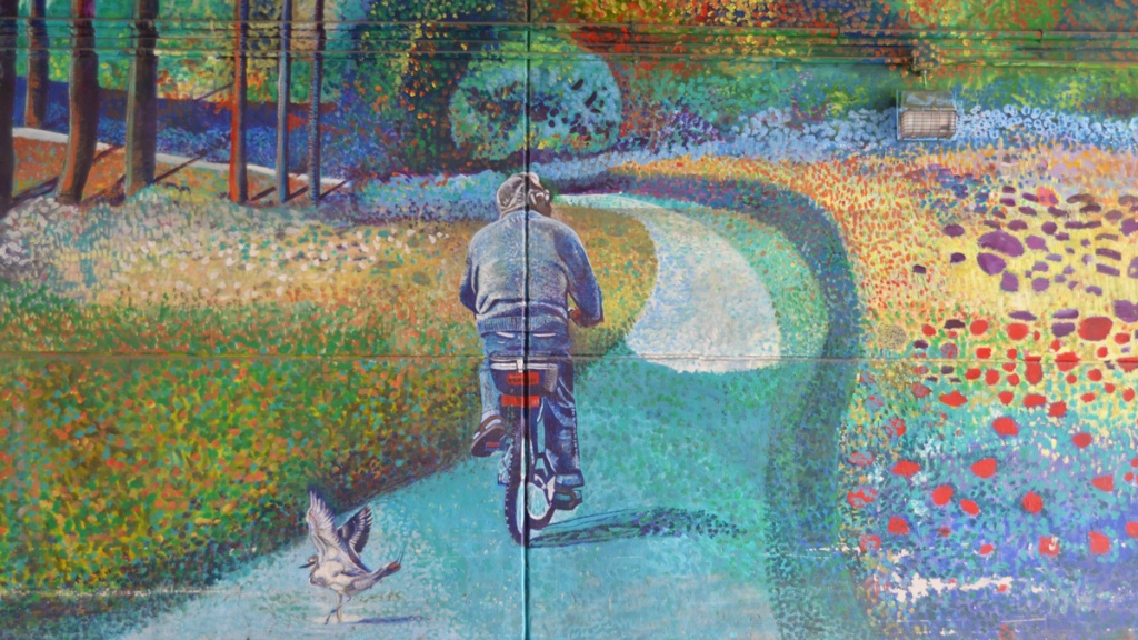 part of a mural, a man cycling on a path, a sea gull lands behind him., path goes past field of flowers