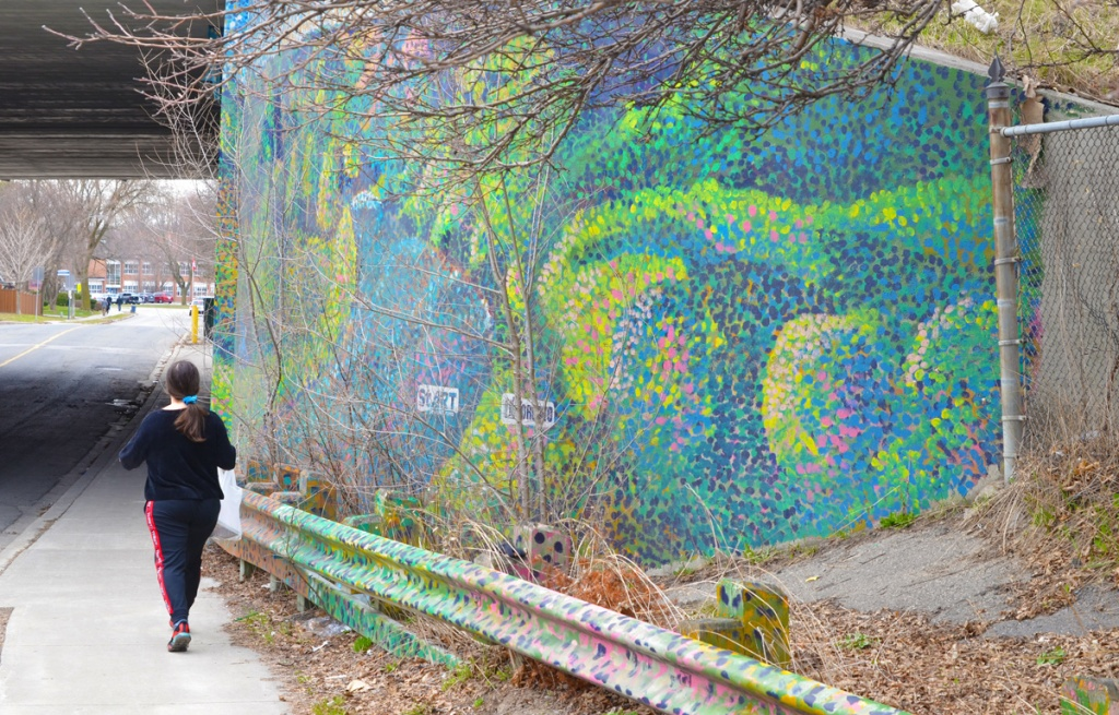 Woman walking on sidewalk, walking past a mural by Start and City of Toronto, on DVP underpass concrete walls