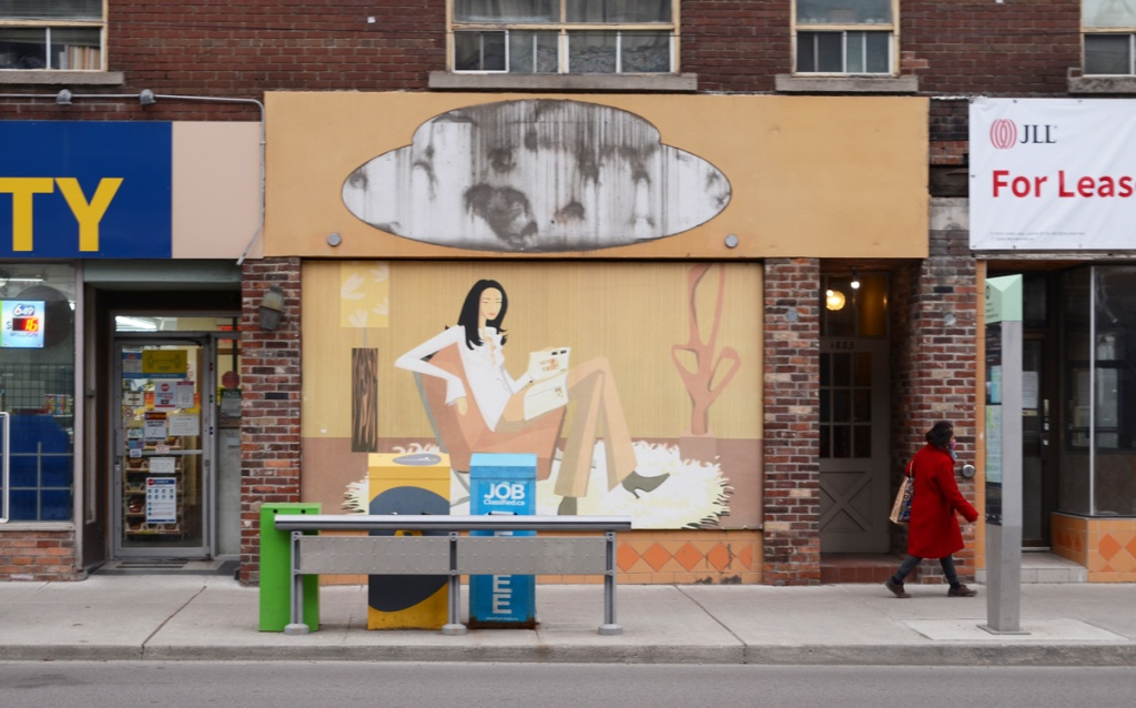 from across the street, mural of a woman on a sofa reading a book, mural, covers window of an empty store, a woman in a red coat is walking past, the store to the right is for lease, the store to the left is a variety store with a blue and yellow sign,