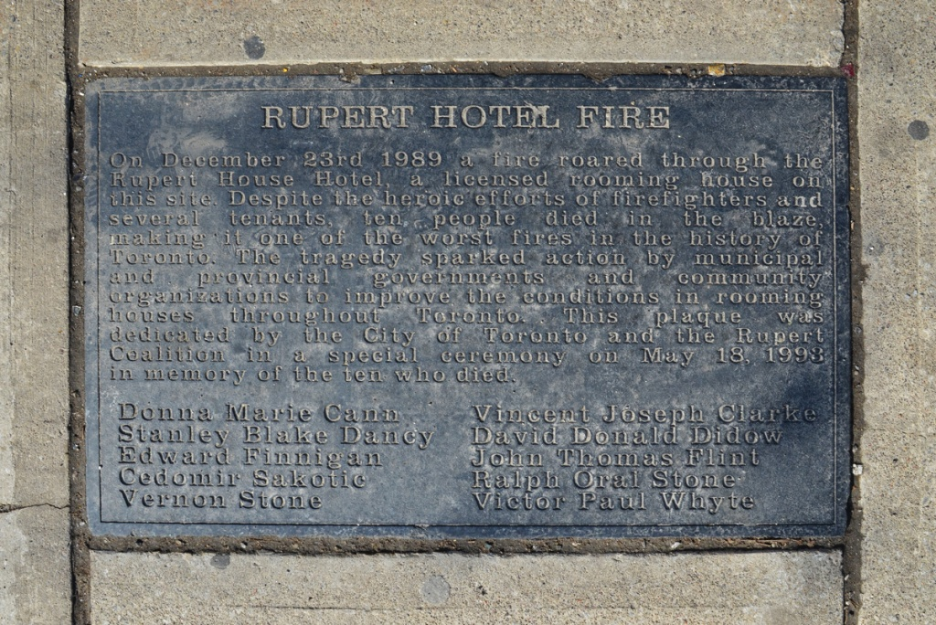 Plaque in the sidewalk describing the Rupert Hotel fire of 1989 when a rooming house burned down, killing 8 people
