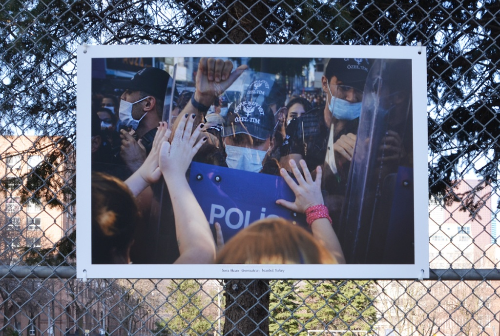 photograph of a protest in Istanbul Turkey taken by Serra Akcan, mounted on a chainlink fence beside a park