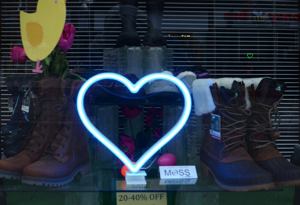 blue LED lights in the shape of a heart in the window of a shoe store on Queen Street East