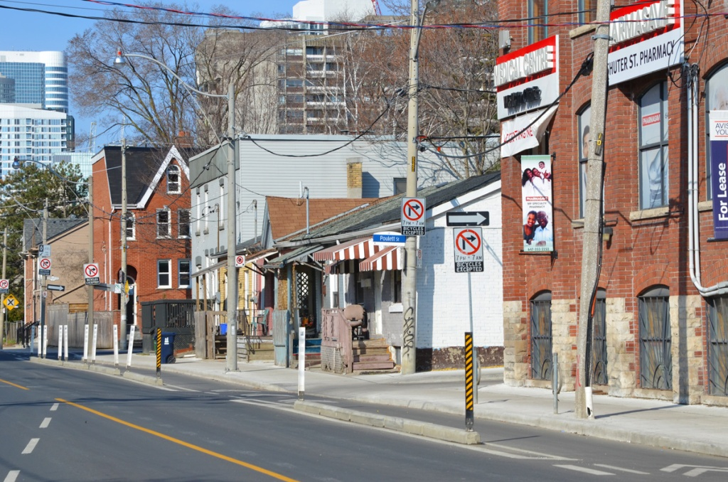 Looking west from Parliament street, the north side of Shuter Street including the Shuter St. Pharmacy, entrance to Poulett St, and some older small houses.  Taller, newer buildings in the background