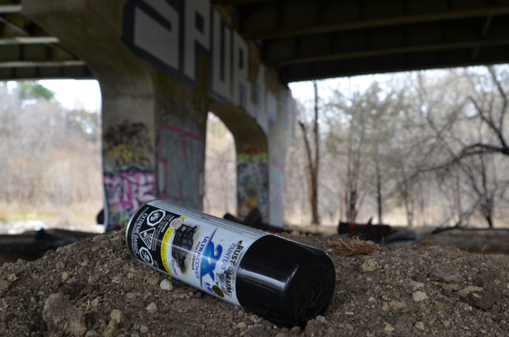 close up of a discarded can of spray paint lying on the ground.  Graffiti under a bridge is in the background but out of focus.