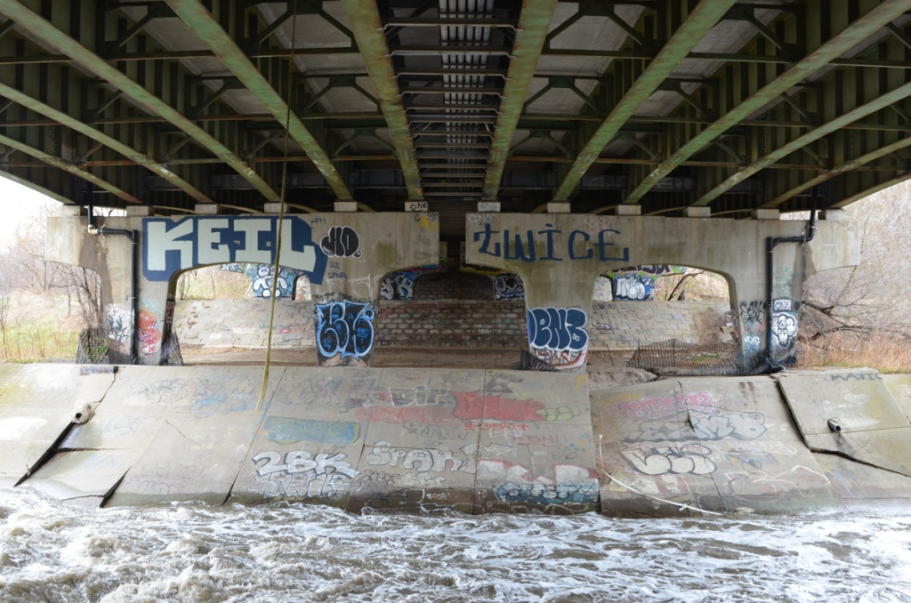 under a bridge over the Don River with graffiti on the concrete, metal girders overhead, water in the river