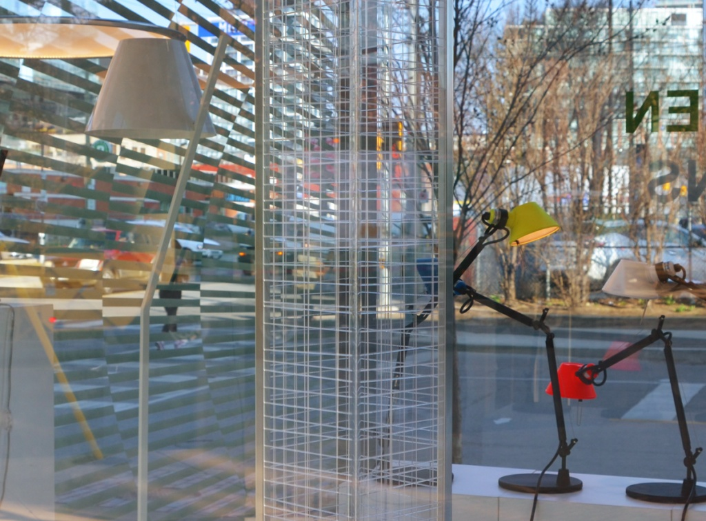 Distillery District lighting store, looking through their windows, with reflections, a person walking past, horizontal lines, yellow and red desk lamps, an oval lamp hanging from the ceiling