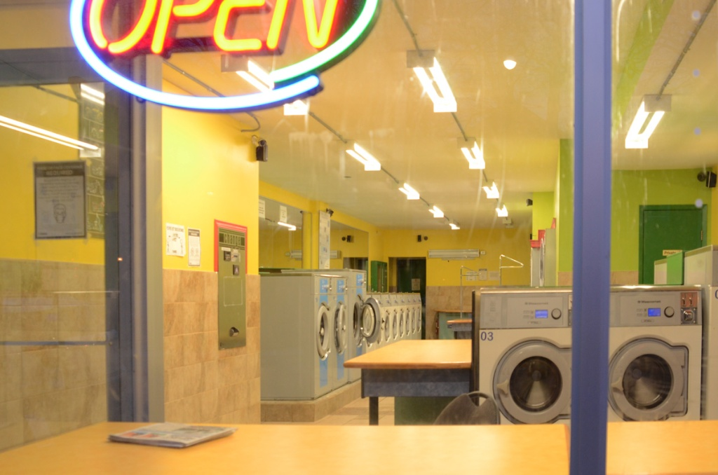looking in the window of a laundromat with no people in it, but with open sign