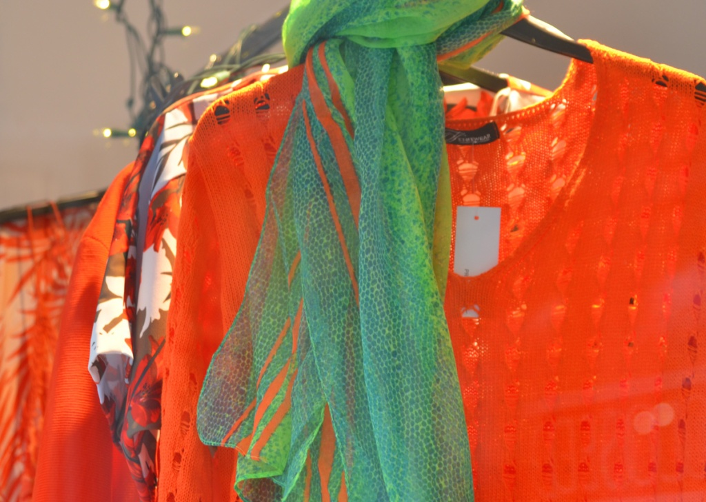 clothing store window with women's tops and blouses in orange hanging from a bar, a green and orange scarf around the neck of the orange knit top in front