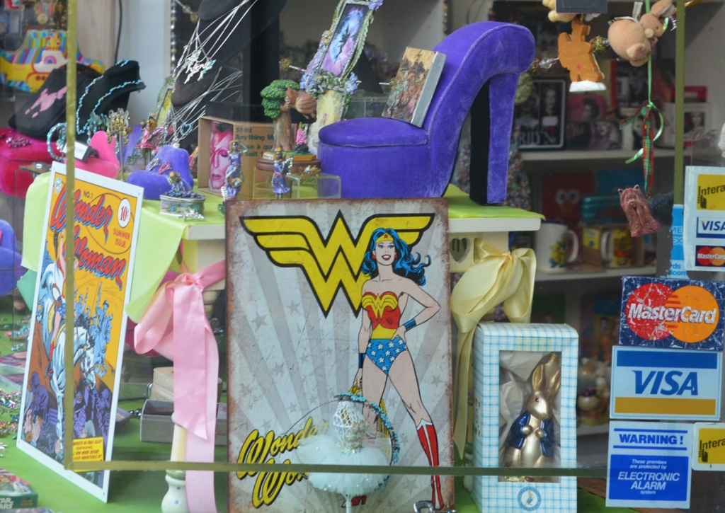 store window, wonder woman items, a large purple platform shoe,