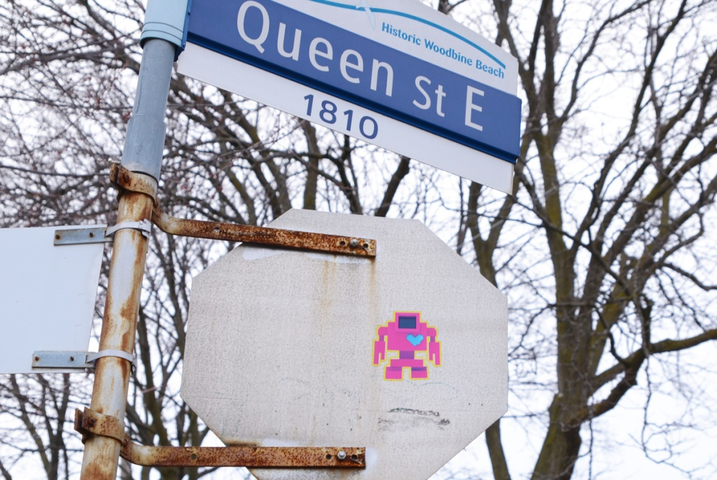 pink lovebot sticker, with a blue heart, on the back of a stop sign, historic woodbine beach street sign for Queen Street East as well