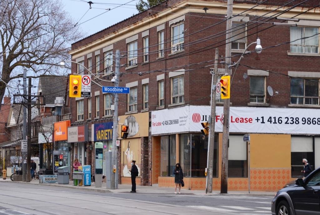 southeast corner of Woodbine and Queen St East, three storey brick building with stores on ground level, people waiting at traffic light,