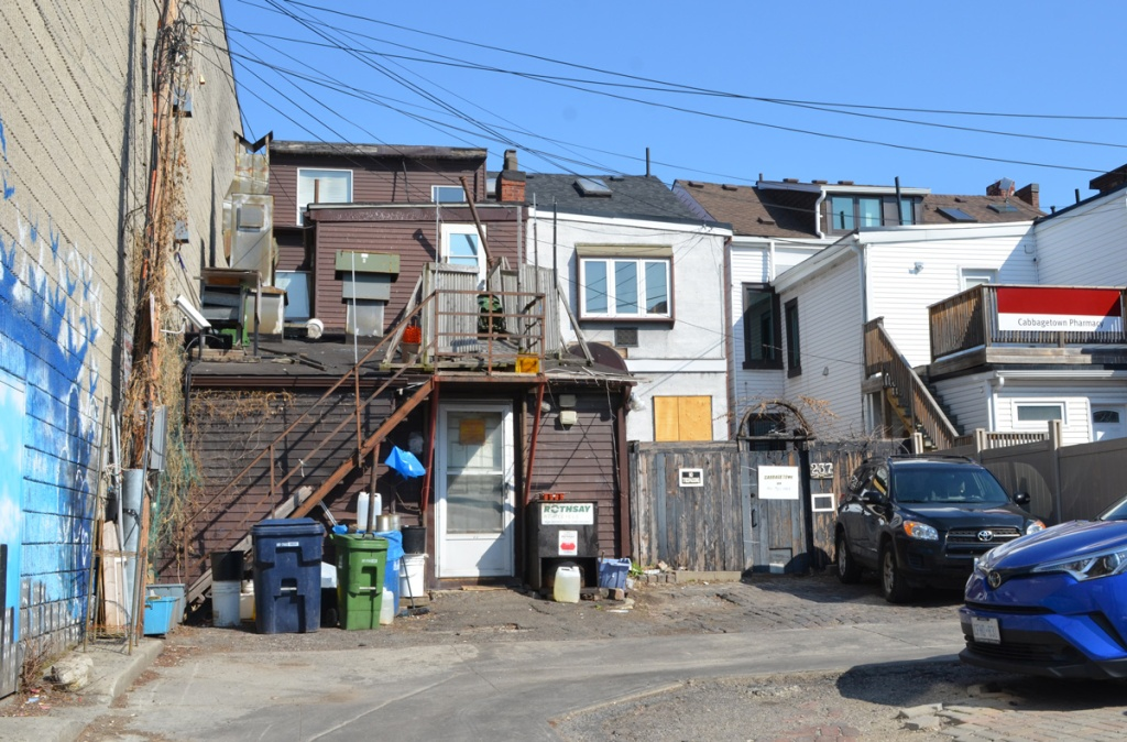 in an alley, view of back of houses with exterior staircases, fences, rubbish bins, parked cars, jumble of lines