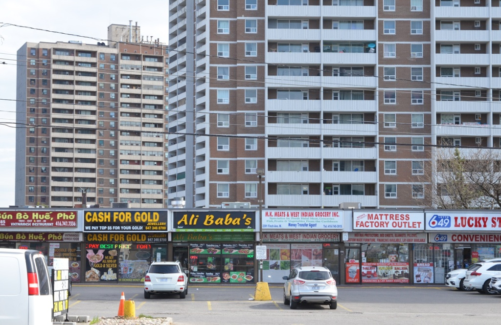 two highrise apartment buildings in red brick with white balconies, strip mall in front with 6 businesses, a vietnamese restaurant, Ali Babas fast food, a west indian grocery, a mattress store, and a convenience store