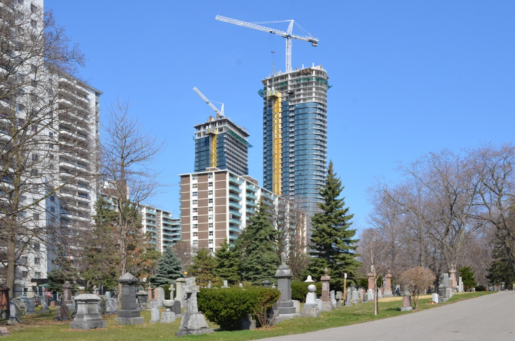 view from inside St. James cemetery, looking over some tombstones and monuments with large highrise of St. James town and newer condo development being built in the background, cranes, under construction,