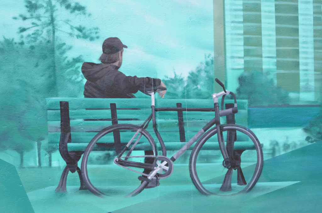painting of a young man sitting on a bench, with his bicycle leaning against the back of the bench, an apartment building in the background, part of a mural featuring views of the east end of Toronto