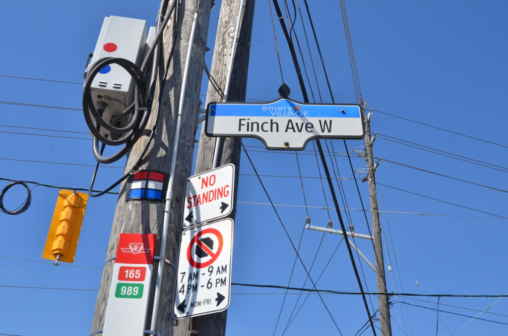 utility pole with police red light camera, no standing sign, a TTC bus stop, and a street sign for Finch Ave West in Emery village