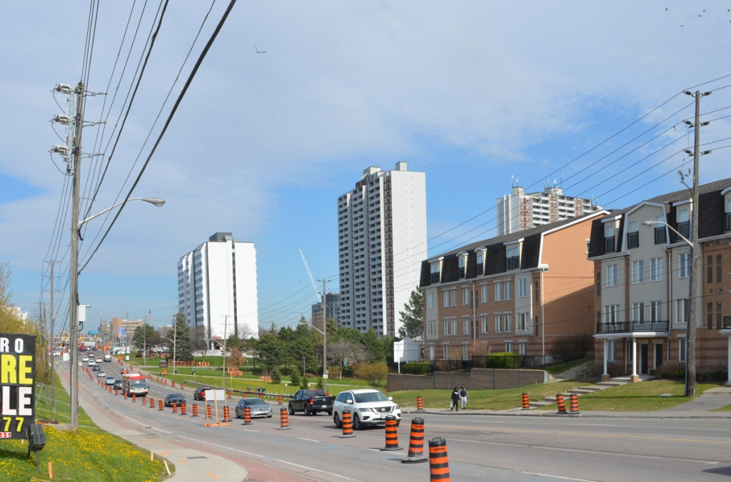 Finch Ave West looking east towards Weston Road, townhouses on the south side of the street, orange and black construction cones on both sides of the street, some traffic, apartment buildings in the background