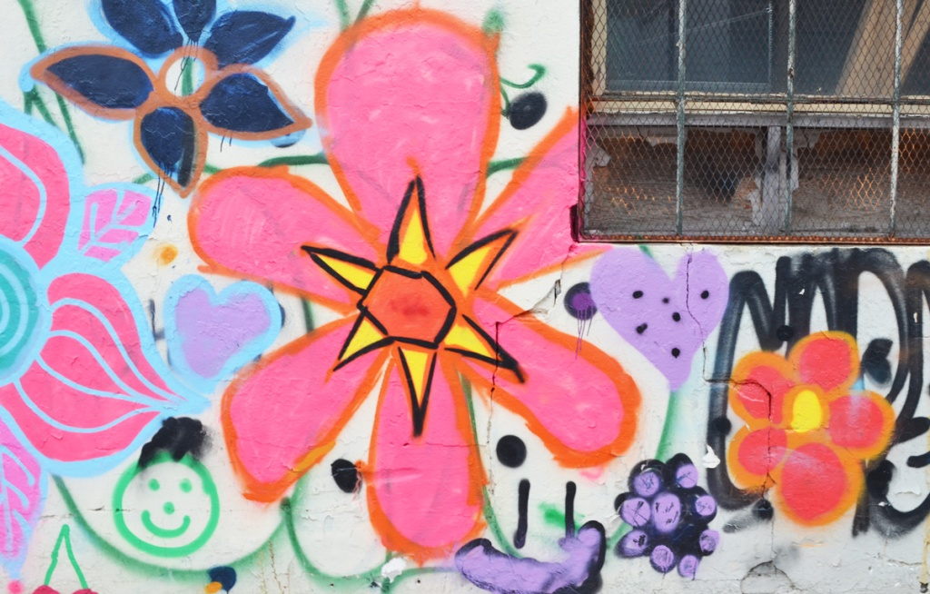 painted, large 6 petal pink flower with yellow triangles at central edge, and an orange hexagon center, on same wall, a green happy face
