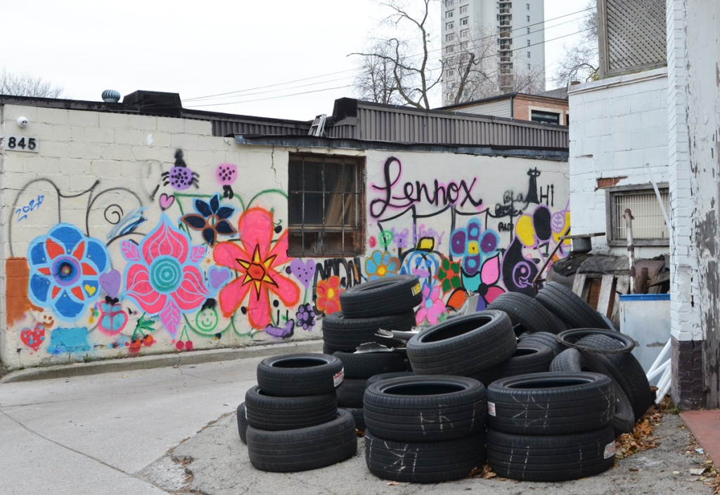 a pile of tires in an alley across from a white wall painted with lots of colourful flowers, stylized form