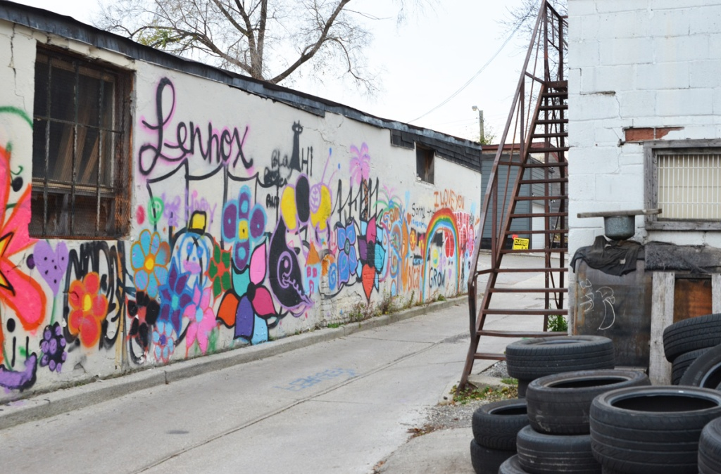 alleyway with metal exterior stairs to upper floor, a pile of tires, and a wall full of colourful flowers and a rainbow