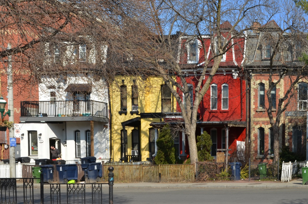 old heritage row houses - one white, then yellow, then bright red, then red brick