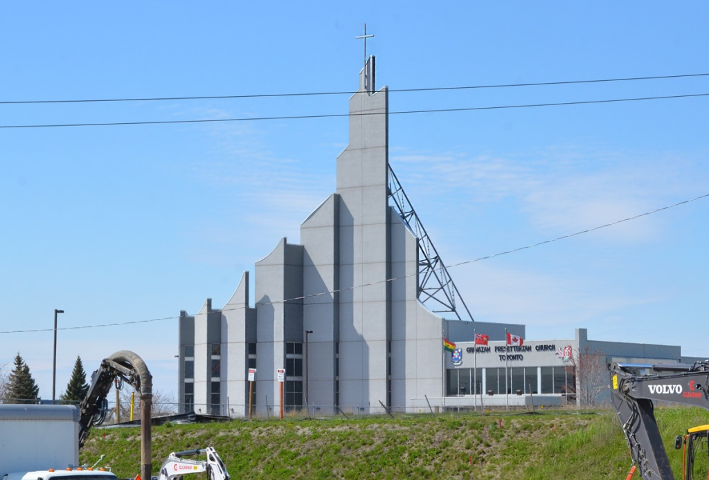 Ghanaian Presbyterian church, light grey concrete structure with front in a triangle shape, cross on top of the tallest middle section, three flags in front - Canada, Ontario and Ghana