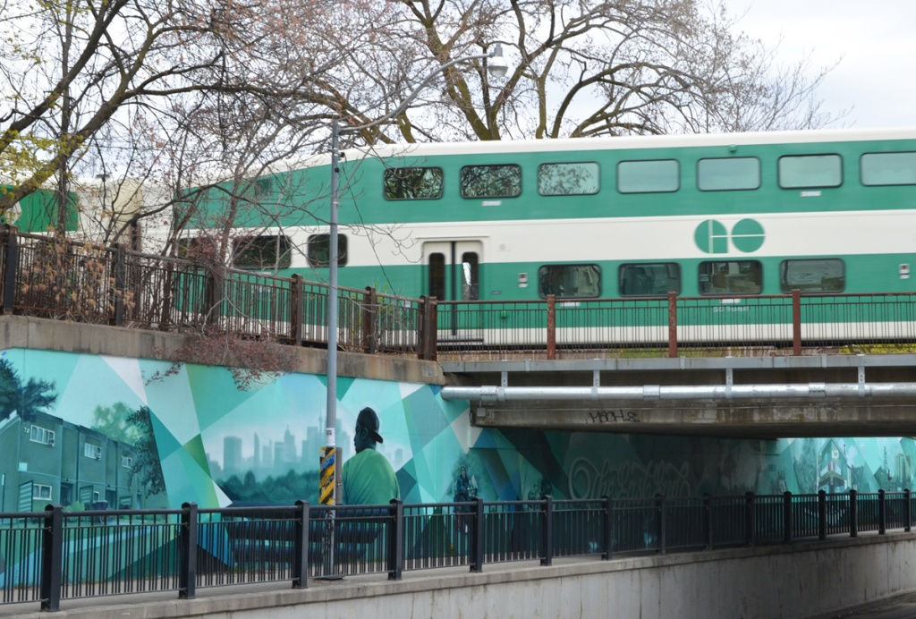 green and white GO train passing over bridge over Jones Ave. where a mural in shades of green and blue has been painted
