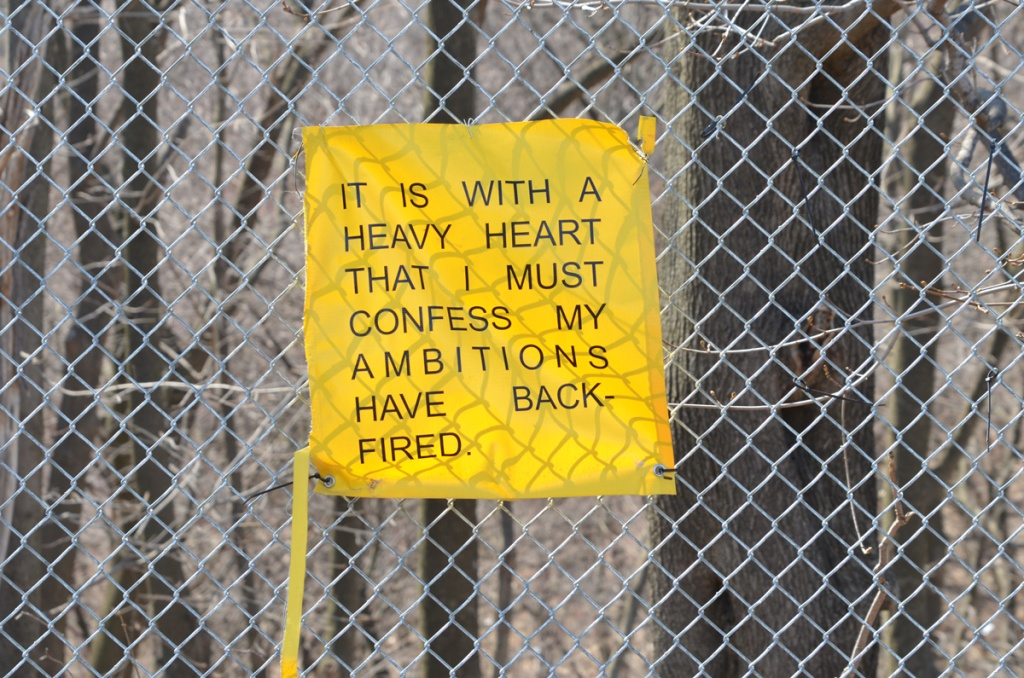 yellow poster with words on a chain link fence  words say it is with a heavy heart that i must confess my ambitions have backfired