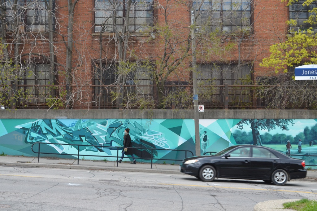 a woman is walking past a mural on Jones Ave., also a black car is on the street, East End mural