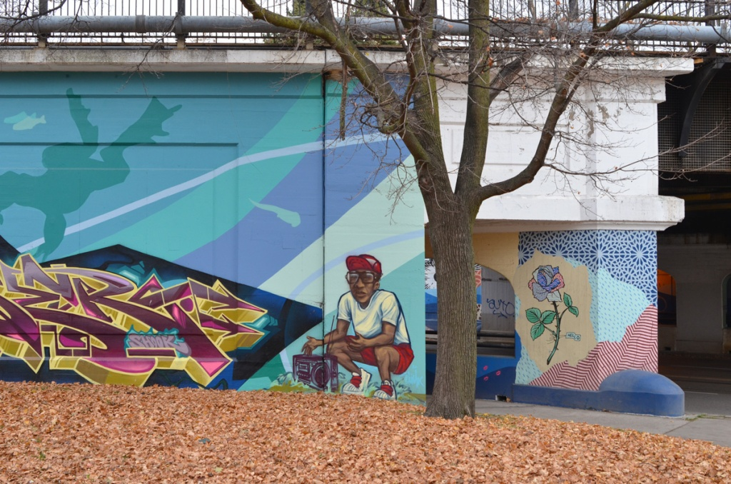 part of a mural, a young man in red shorts and red baseball cap, squatting on ground beside a ghetto blaster, there is also part of a text street art piece, as well as a rose on a stem with thorns and a couple of leaves painted on a support pillar for a bridge