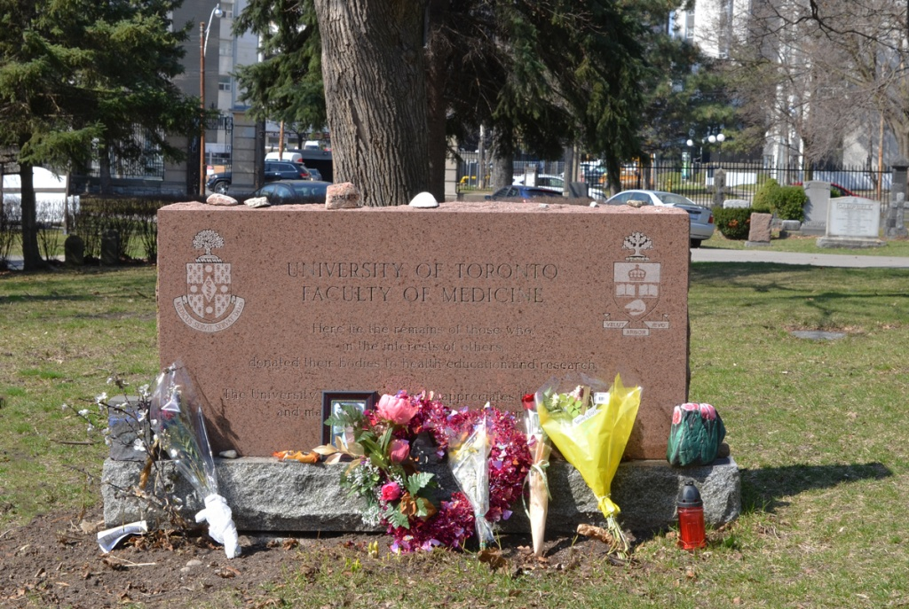 grave marker in St. James cemetery with bouquets of flowers around the bottom, University of Toronto faculty of medicine memorial for those who gave bodies to medical research, remains are buried here