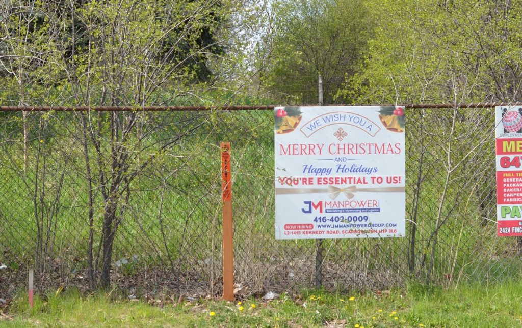 sign on a chainlink fence wishing a merry christmas and happy holidays to essential workers - you essential to us,