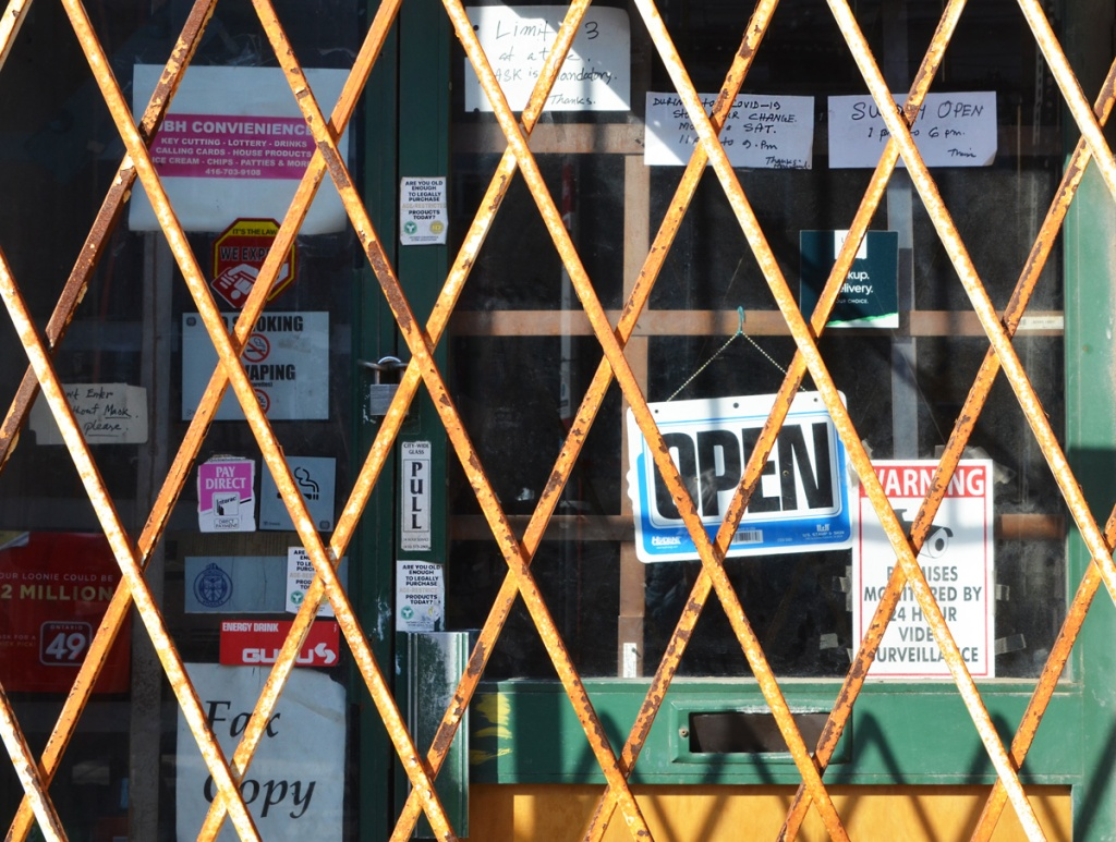rusty yellow metal grille closed in front of a store front with an open sign, ans some had written signs re opening hours