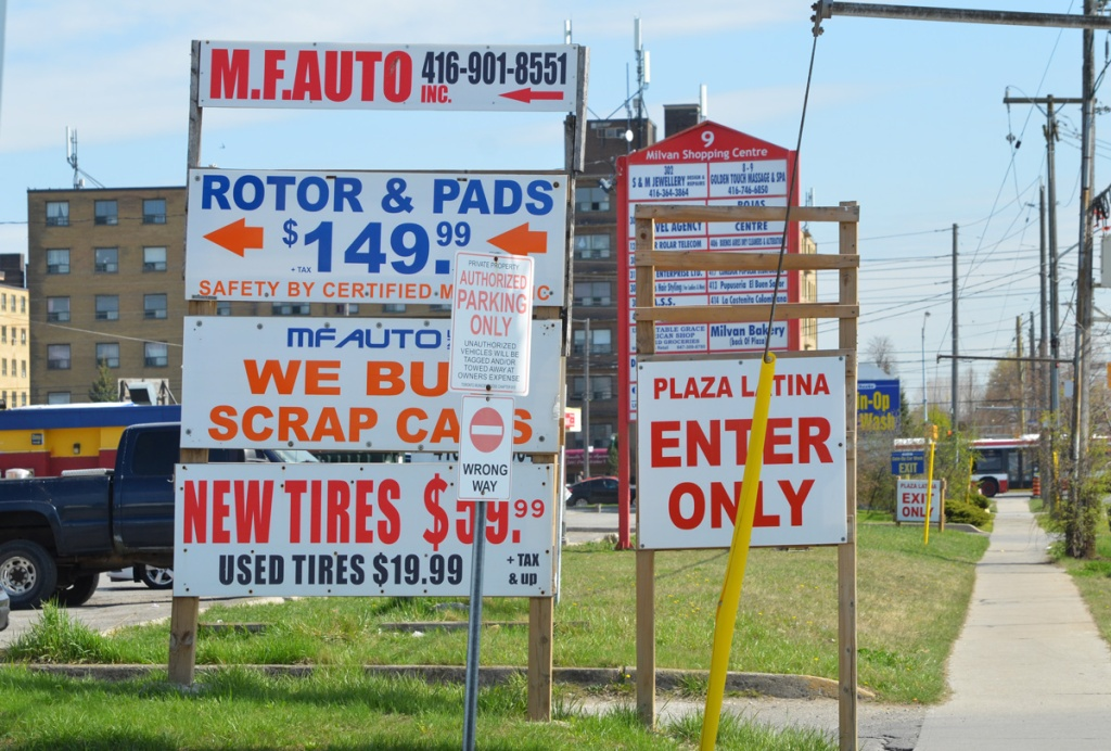 many signs beside a sidewalk, new tires, rotors and pads, Plaza Latina, milvan shopping centre, a bus in the background