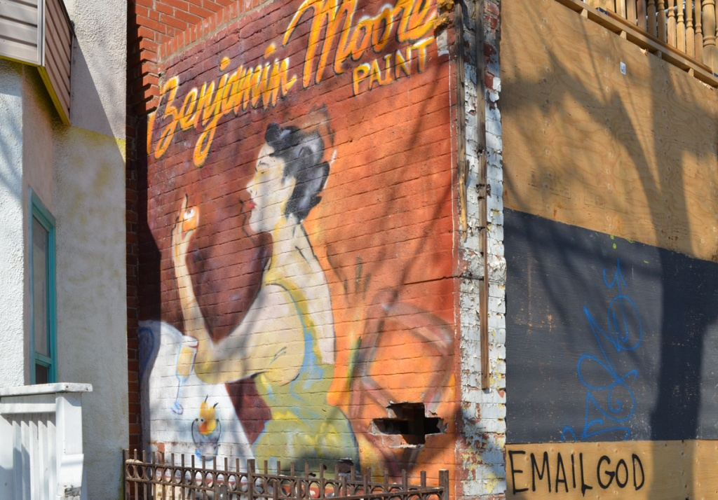 mural of a seated woman on a brick wall, an advert for Benjamin Moore paint