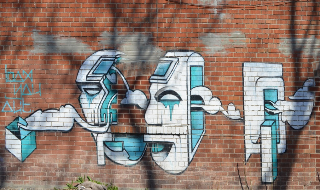 mural on a brick wall in white and turquoise of a stylized head divided into sections,