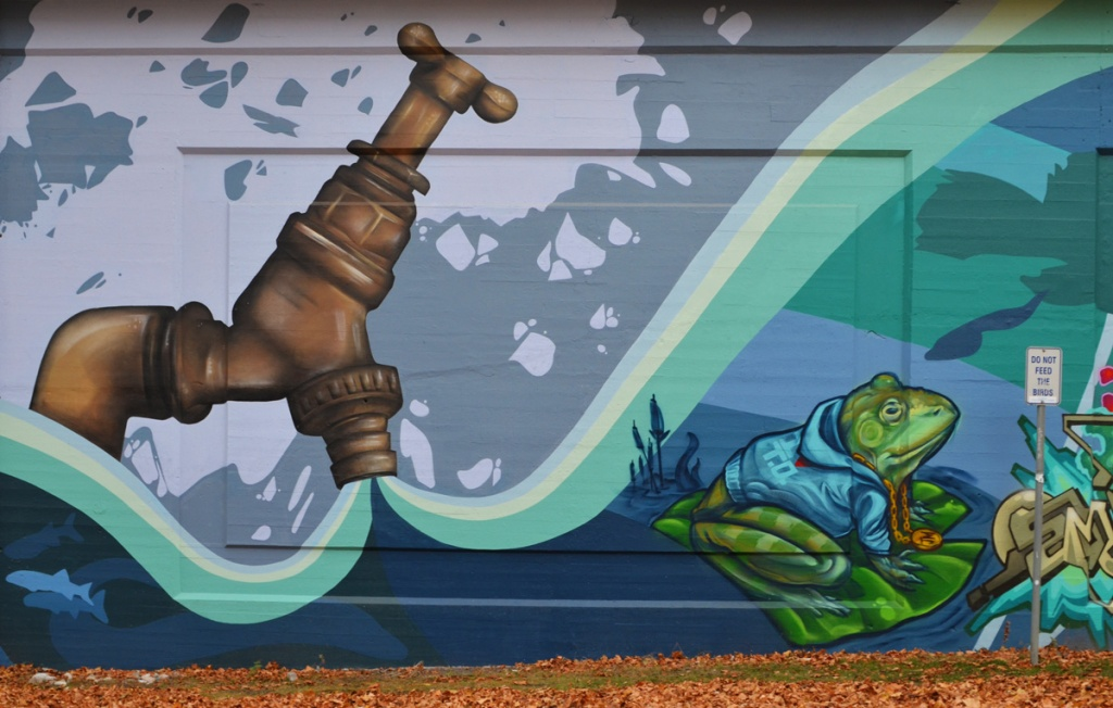 part of a mural, a very large brass faucet is open, water is pouring out, a frog sits on a lily pad