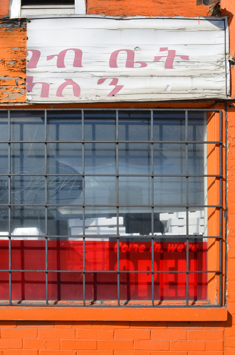 orange storefront with window.  metal grille over window, red plastic in bottom of window, broke sign in different alphabet over the window