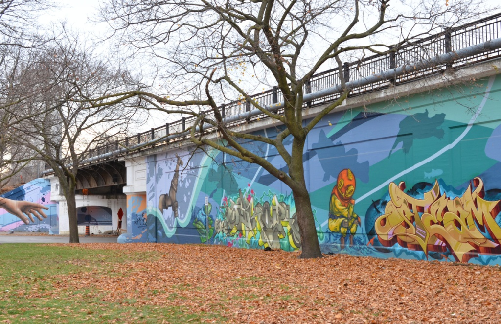 mural on a wall along railway embankment, park in front of wall.  water theme mural, large faucet has water running out of it, a frog, a scuba diver, and some text street art
